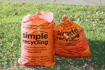 Two Orange Simple Recycling Bags on a Lawn